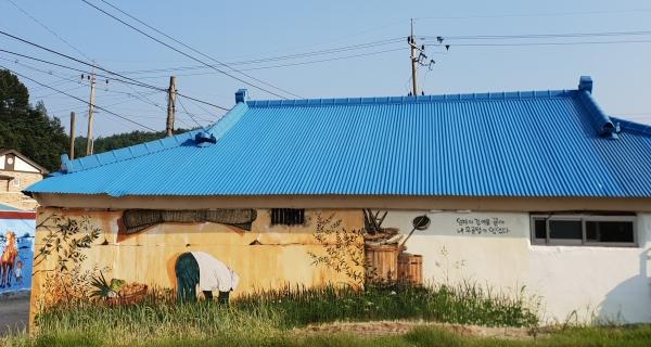 집앞에 있는 파밭과 벽화가 어우러져 마치 벽화 속 어른이 파를 뽑는 듯한 풍경을 만들어 낸다.